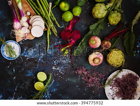 Purple and green veggies and roots composition on a dark slate table. Artichoke, Beetroot, red onion, radish, asparagus ready to prepare salad. detox and diet food. - stock photo