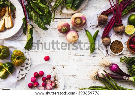 Purple and green veggies and roots composition on a rustic white wooden table. Beetroot, red onion, radish, asparagus, green tomatoes, parsnip, parsley ready to prepare salad. detox and diet food. - stock photo