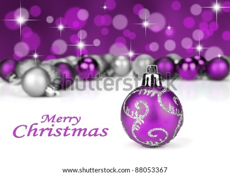 Purple and silver Christmas baubles with stars and and glitter in the background - stock photo