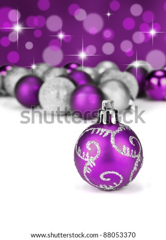 Purple and silver Christmas baubles with stars and and glitter in the background