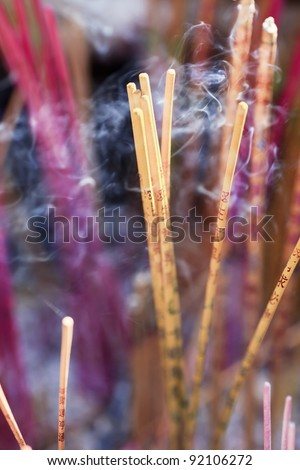 Purple and yellow incense sticks burning at an altar of a Taoist temple, Beijing, China - stock photo