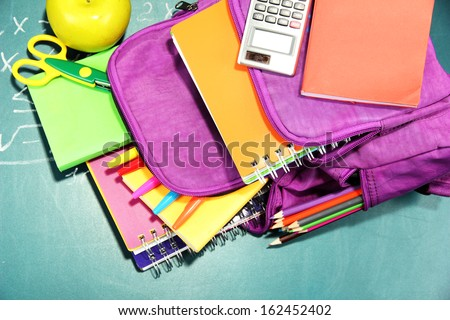 Purple backpack with school supplies on green desk background - stock photo