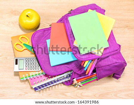 Purple backpack with school supplies on wooden background - stock photo