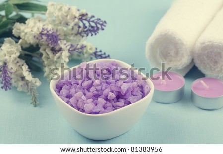 purple bath salt, towels and candles on a blue background - stock photo