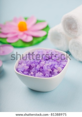 purple bath salt, towels and flowers on a blue background - stock photo