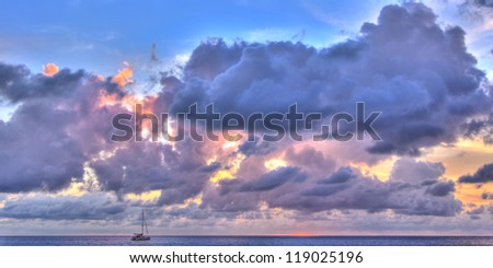 Purple cast panorama of sunset in ocean with yacht - stock photo