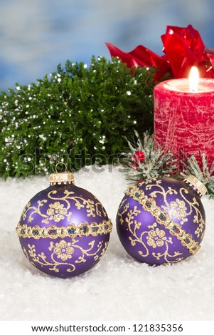 Purple christmas ornaments in snow with a red holiday candle behind them