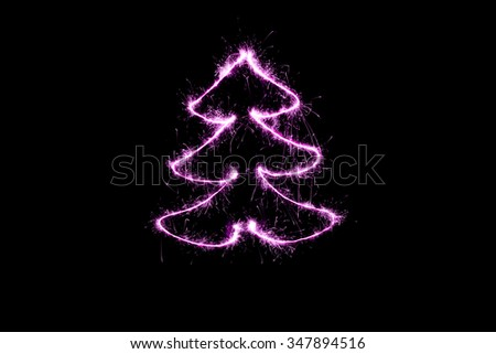 purple Christmas tree made by sparkler on a black background - stock photo
