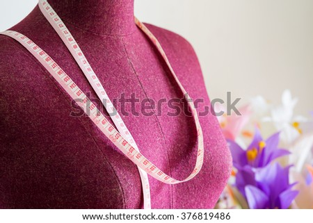 Purple clothing mannequin with measuring tape and colorful flowers vase on white cement wall background - stock photo