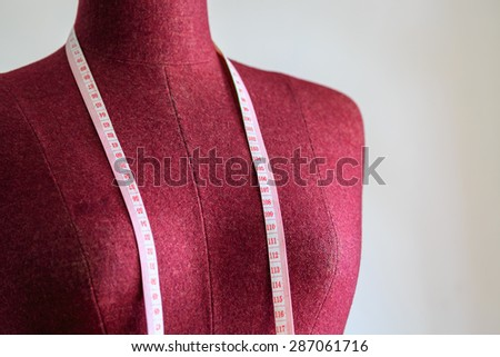 Purple clothing mannequin with measuring tape on white cement wall background - stock photo