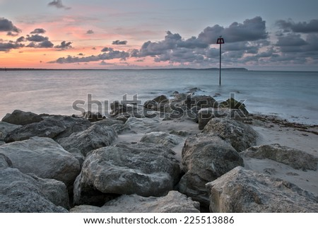 Purple cloudy sunrise at the seashore, with a sea defence groyne. Hengistbury Head, Hampshire, UK. - stock photo