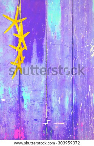 Purple colorful vintage background with shabby distressed grungy texture hippie style decorated with yellow starfish hanging from a straw string.  - stock photo