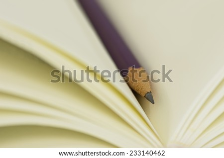 Purple Crayon cross between the pages are blank.  - stock photo