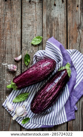 Purple eggplant (aubergine), garlic and basil leaves on vintage wooden table from above. Fresh harvest from the garden in rustic kitchen. Background layout with free text space. - stock photo