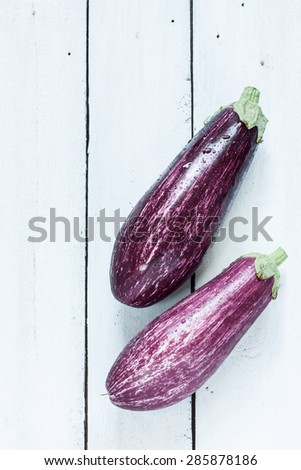 Purple eggplant (aubergine) on white planked wood table from above. Fresh harvest from the garden. Background layout with free text space. - stock photo