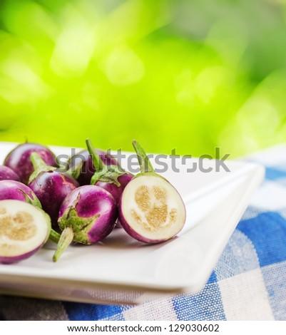 Purple eggplants on nature background. - stock photo