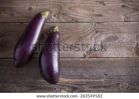 purple eggplants on wooden background - stock photo