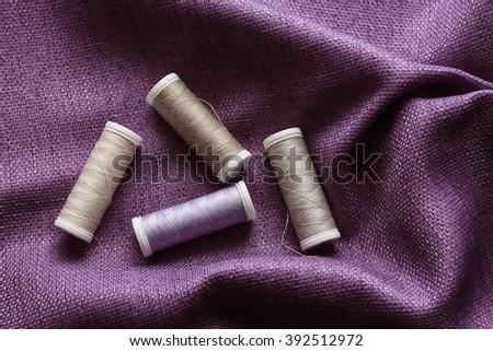 Purple fabric and threads - stock photo