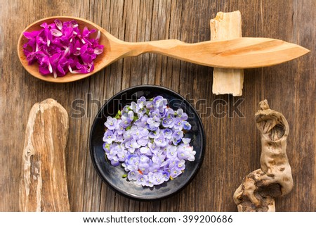 purple flower petals plants dead-nettle in a wooden spoon and pale blue flowers Persian speedwell on an old wooden board close up. view from above. aromatherapy, herbal tea, homeopathic medicine - stock photo