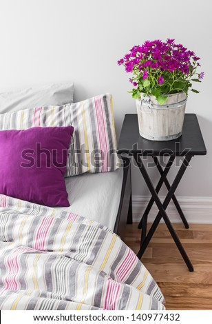 Purple flowers decorating a bright contemporary bedroom. - stock photo