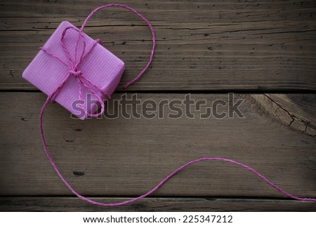 Purple Gift With Purple Ribbon On Wooden Background - stock photo