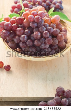 Purple Grapes Fruit in a bamboo basket And cutting boards made of wood.