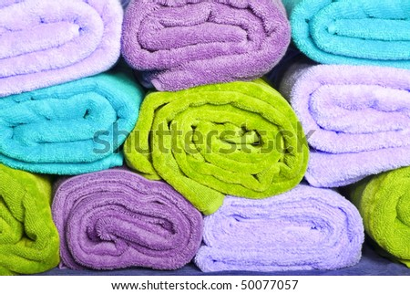 Purple, green and blue towels stacked up