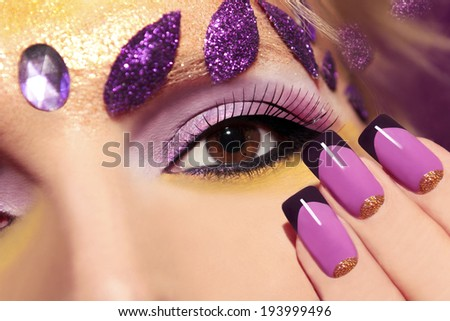 Purple makeup and nails with gold sequins and decoration in the form of leaves.