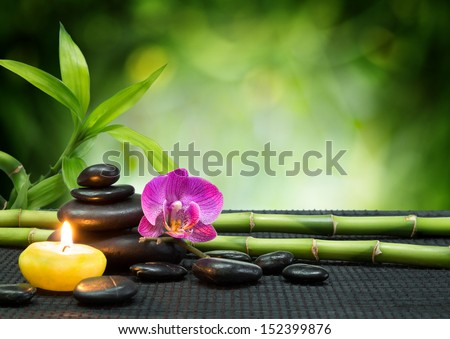 purple orchid, candle, with tower black stones , bamboo on black mat - stock photo