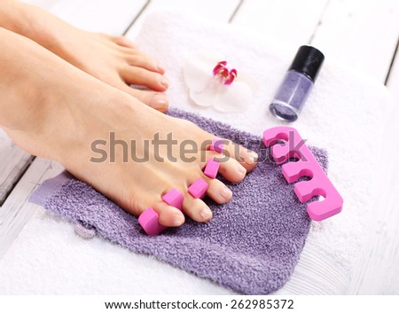 Purple pedicure, groomed female foot. Foot care treatment and nail, the woman at the beautician for pedicure. - stock photo