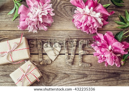 Purple peonies with letters LOVE and gift boxes on old wooden boards. Place for text. Top view. - stock photo