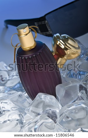Purple perfume bottle lying on ice with a pair of sun glasses in the back - stock photo