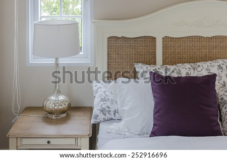 purple pillow on wooden bed  with lamp in bedroom at home