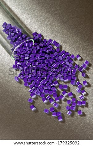 purple Polymer Granulate on stainless steel sheet in laboratory - stock photo