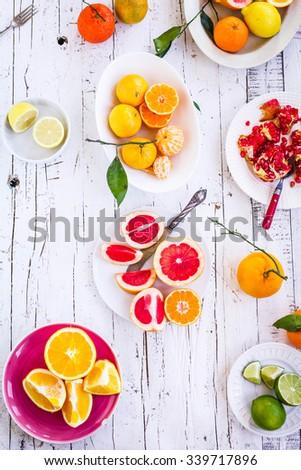 Purple, red  and orange fruit background in bowls. Lime, pomegranate, tangerine, orange, mandarin, grapefruit, lime, lemon sliced above white rustic wooden table. Copy space. - stock photo