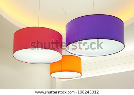 Purple, red and orange round stylish lampshades hang from ceiling - stock photo