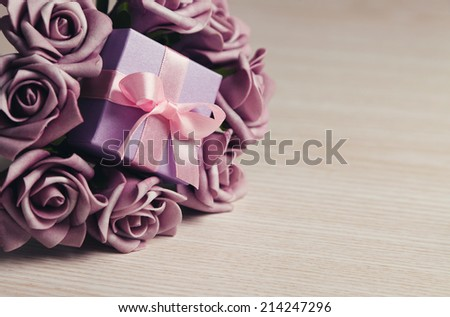 purple roses and gift box with pink ribbon on wooden surface - stock photo