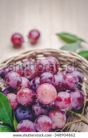 purple round grapes on old wooden table , vintage