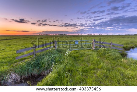 Purple sunset over fence in flat countryside near Groningen - stock photo