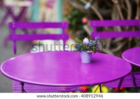 Purple table of Parisian outdoor cafe decorated with little bucket, flowers and Easter egg - stock photo
