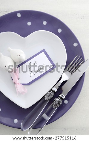 Purple theme wedding table place setting with heart shape plates and vintage silverware.
