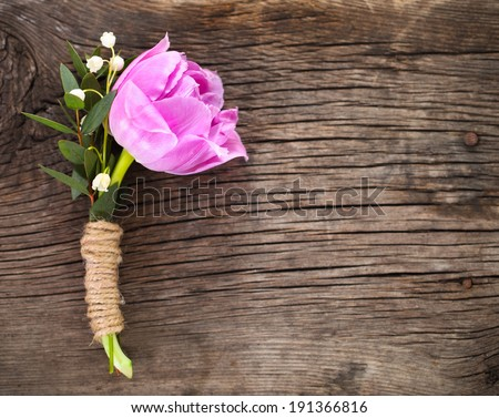 Purple tulip buttonhole for groom on the wooden background. Close up - stock photo