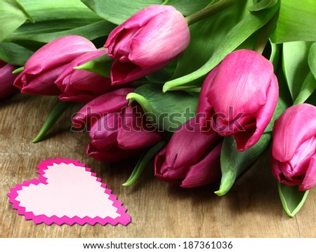 Purple tulips on a wooden background with heart