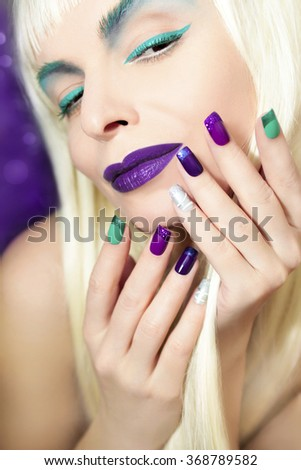 Purple turquoise makeup and a French manicure with colored sequins.