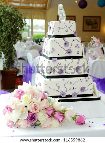 Purple wedding cake with brides bouquet at reception - stock photo