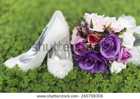 purple wedding flowers and bridal shoes - stock photo