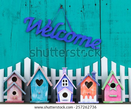 Purple welcome sign hanging over white picket fence with row of colorful birdhouses with antique teal blue wooden background - stock photo