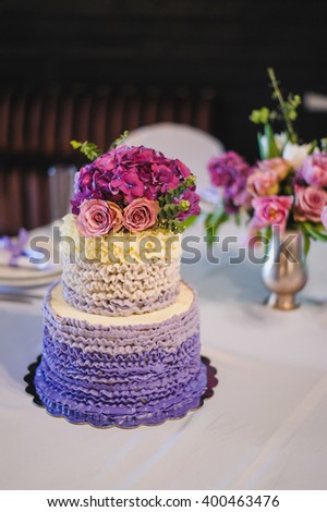 purple white wedding cake decorated with flowers on festive table