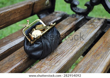 Purse full of coins worth on the bench. Found purse. - stock photo
