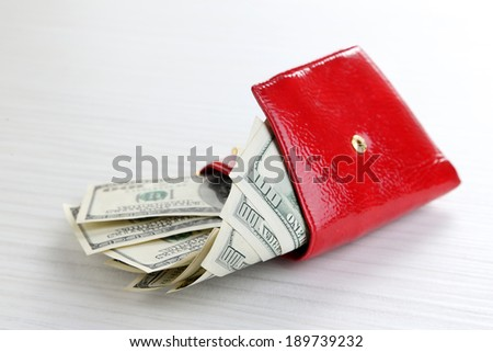 Purse with dollars banknotes on wooden table - stock photo